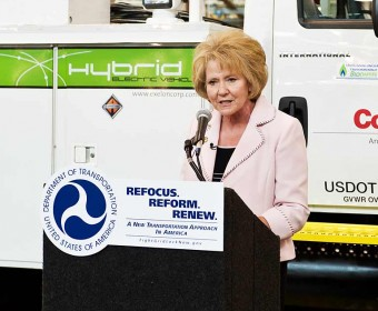 speaker at podium truck in background